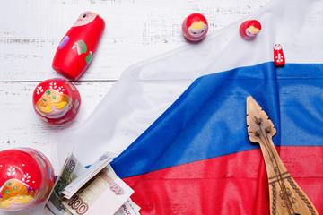 Russian symbols matryoshka, balalaika, rubles cash and flag of russian federation on wooden background.