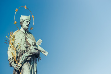 Figure of Saint with cross at Old Town Charles (Karluv most) Bridge Tower in Prague, Czech Republic
