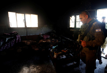 Israeli soldier inspects the damage to the house of Palestinian Dawabsheh family after it was torched in the village of Duma near Nablus, in the occupied West Bank