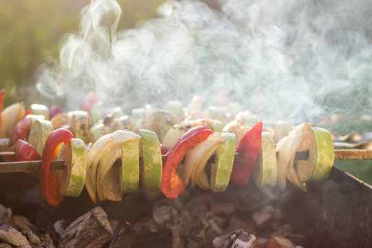 Grilled vegetables, zucchini, onions and red pepper, with lots of smoke cooked on fire outdoors, hot, sun light, backlight golden hour, summer garden party, harvest and farming, organic  food concept