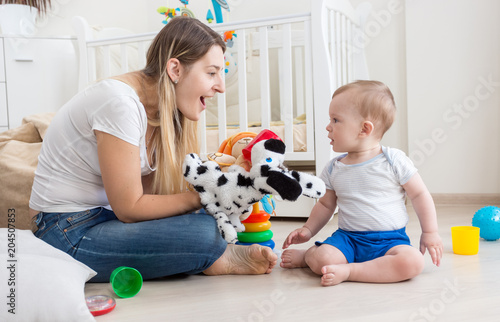 Attractive Young Smiling Woman Playing With Her Little Son On Floor At Bedroom