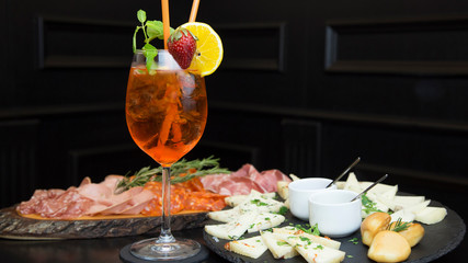 Traditional italian aperitif with proscioutto, mortadella sausage, cheese and aperol spritz drink