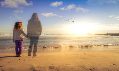 Una niña sujeta la mano del espiritu de su madre muerta mientras contemplan la puesta de sol Fototapete