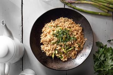 Potrawa z brązowego ryżu i szparagów podana na talerzu.