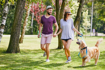 Obraz Young couple walking their dog together in the park during summer - fototapety do salonu