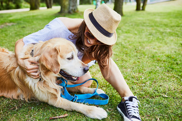 Young woman sitting on the ground with her dog in the park during summer
