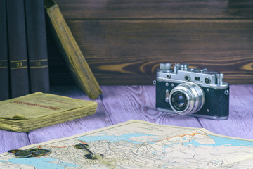 Retro-style. Old books and a map on the table. Film camera and a handful of coins.