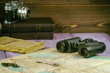 On the table lay an old book, map, coins, a key and a pair of binoculars. Also there is a film camera.