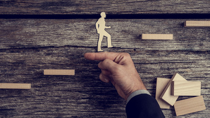 Businessman supporting paper cut out of a man climbing stairs