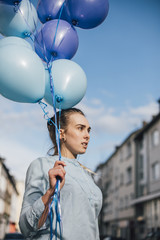 Portrait of woman with blue balloons