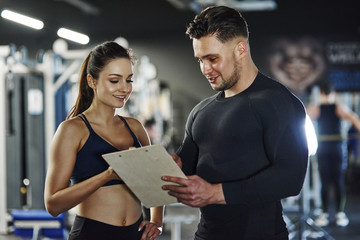 Personal trainer talking to woman in gym