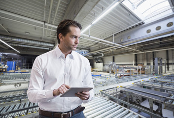 Businessman using tablet on factory shop floor