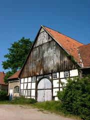Alter Bauernhof mit Fachwerk und spitzem Giebel vor blauem Himmel bei Sonnenschein in Hagen bei Lage im Kreis Lippe in Ostwestfalen