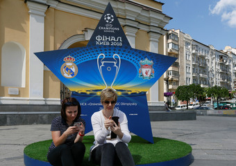 Women use their mobile devices as they sit  in front of the logo of the Champions League Final at the Independence Square in Kiev