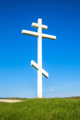 A wooden cross on top of a hill. Orthodox white cross glows on the top of the hill on the background of blue sky and of green grass