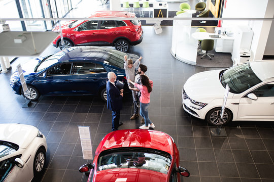 Happy family buying a new car at the car showroom.