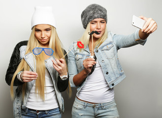 Life style, happiness, emotional and people concept: two hipster girls taking photo. Happy selfie.