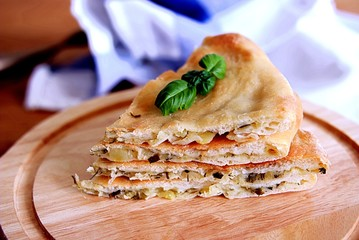 Sliced Ossetian pie with potatoes, cheese and greens
