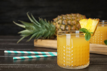 Glass with delicious pineapple juice on table