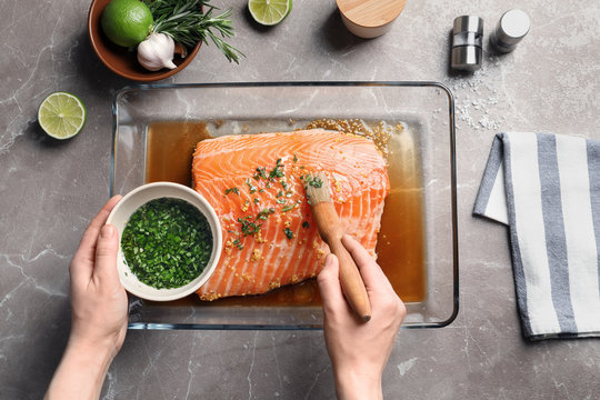Woman marinating raw salmon in dish at table