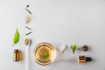 Minimal style. A cup, natural oil, a pipette, vegetable ingredients. Natural cosmetics, handmade skin care. Flat lay