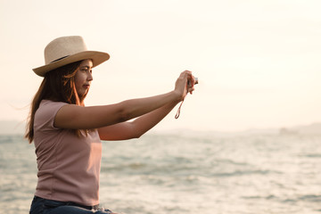 Young happy woman traveler with hat holding digital camera taking photo on sunset sea.