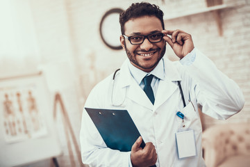 Indian doctor seeing patients in office. Doctor is posing in glasses with clipboard.