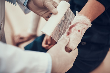 Indian doctor seeing patients in office. Doctor is using bandage on daughter's arm.