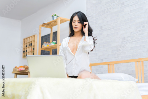 582bfd0a2d6a Sexy asian woman sitting on bed with laptop computer at home. concept of  relax holiday and comfort.