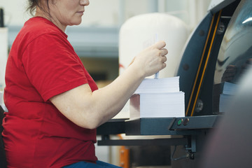Hands of female worker with a stacks of paper in front of printing machinery equipment