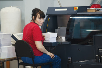 Adult female worker with a stacks of paper in front of print press equipment