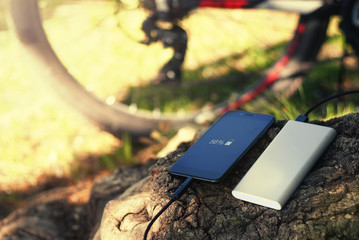 A portable charger charges the smartphone. Power Bank with cable against the background of wood and bicycle