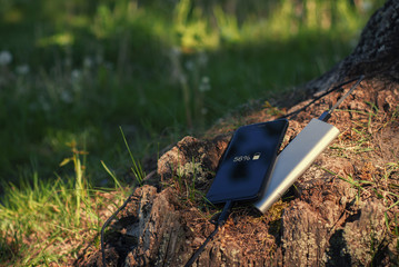 A portable charger charges the smartphone. Power Bank with cable against the background of wood