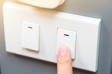 Saving energy concept, someone trying to use index finger to pressing a switch. there is yellow ray light located on top rigth of frame.Pointing finger