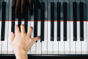Close-up of woman hands playing piano - top view