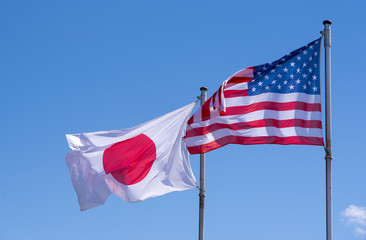 American and Japanese Flags waving against blue Sky