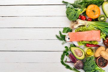 Fish and fresh vegetables. Healthy food. On a white wooden background. Healthy food. Top view. Copy space.