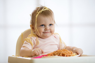 Little baby girl eating her lunch and making a mess