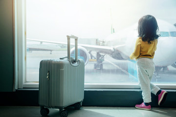 Kids Traveling Concept. Backside of A Two Years old Girl Waiting for Boarding in Airport Terminal and Looking Airplane through Wide Glass Window