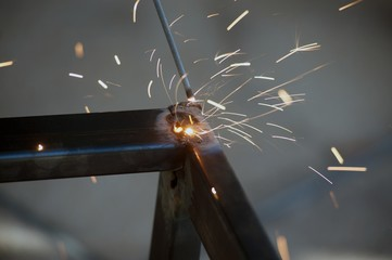 Worker is welding sparks table steel in factory.