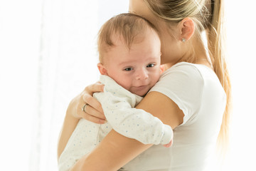 Portrait of cute 3 months old smiling baby boy hugging mother