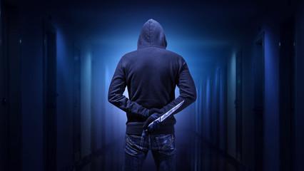 Criminal or bandit holding a knife. - fototapety na wymiar