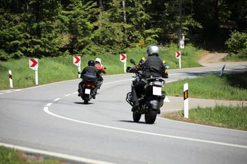 Gruppe von Motorradfahrern auf einer kurvenreichen Landstraße