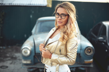 a beautiful blonde with long hair in white denim shorts stands near an old retro car