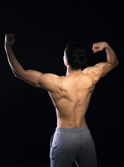 Young muscular man posing. View from back. Black background.