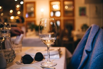 glass in the evening on the table in the restaurant. concept of a lonely date.