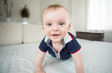 Wide angle closeup portrait of cute smiling baby boy looking in camera