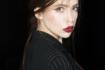 Femininity concept. Girl on strict confident face in black jacket, black background. Woman with stylish makeup and hairstyle. Lady with red lips looking at camera, close up, copy space.