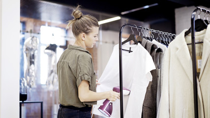 A young blonde girl worker in a clothing store shope is steaming clothes a white shirt in a market place