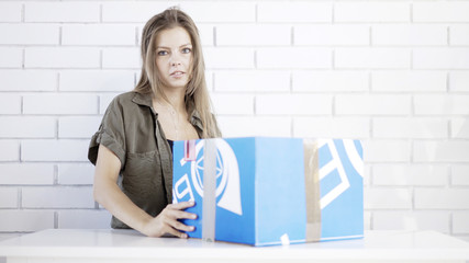 A young disappointed woman opening a blue cardboard box with a box cutter at home delivered gift by air mail looking